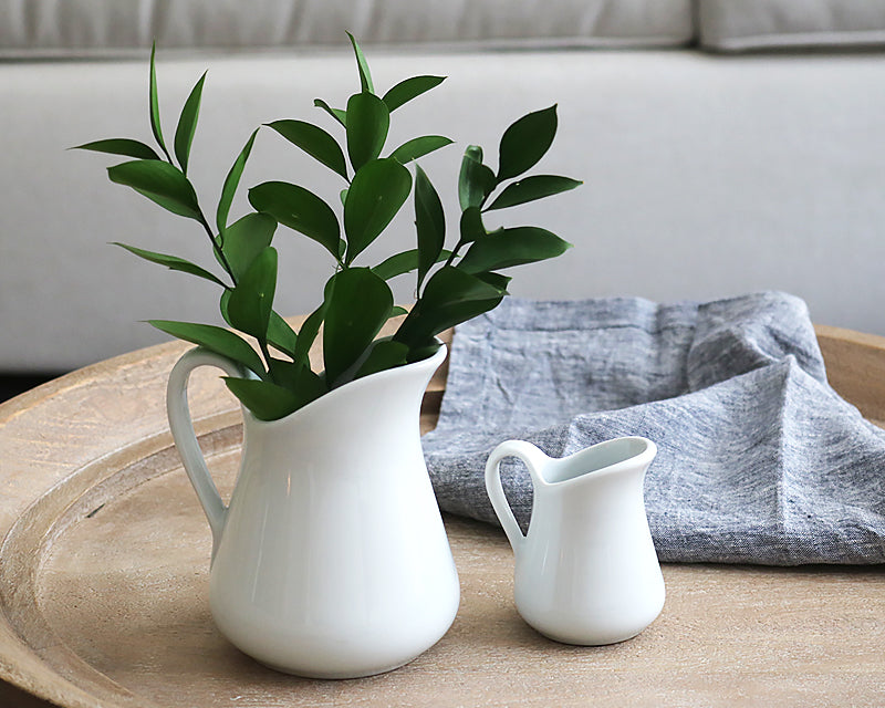 Two milk jugs sit on a table with a linen napkin