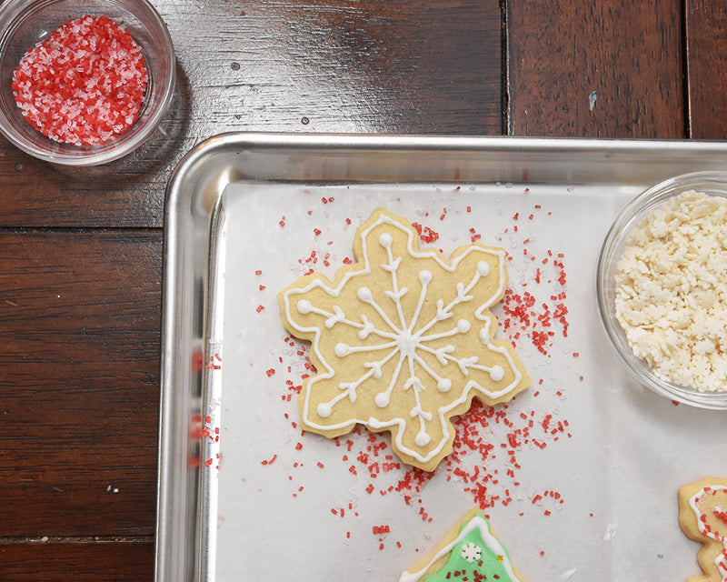 A snowflake cookie on a sheet pan lined with Parchment baking sheet