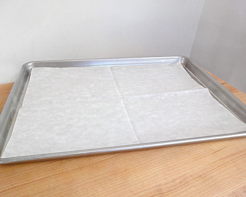 A half sheet pan lined with Parchment Baking Sheet.