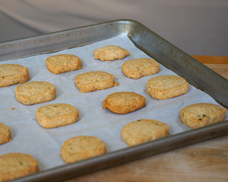 Parmesan Thyme crackers on a half sheet pan lined with Pre-cut parchment paper.