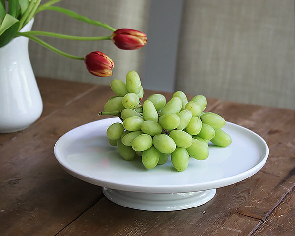 White Cake Stand by Pillivuyt sits on a wood table filled with green grapes. A great way to have the kids eat fruit!