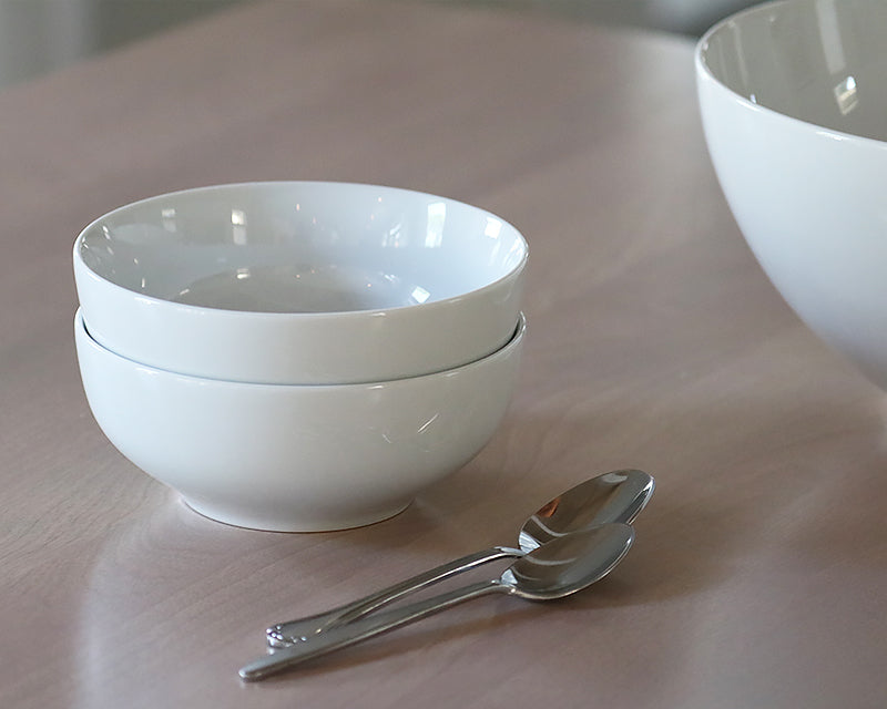 Two white cereal bowls from Pillivuyt stacked next to two spoons