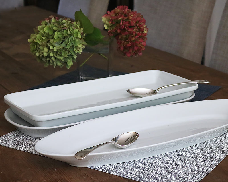 Oversized Platters with Hotel Silver Vibtage Kitchen Spoons sit on a wood dining table ready for use.