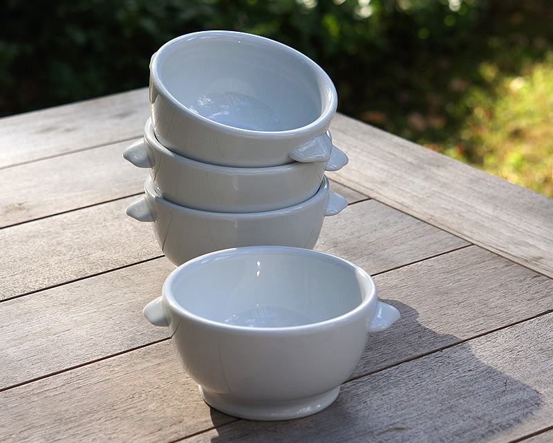 Four white porcelain classic onion soup bowls sitting on outdoor table