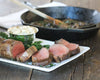 Lodge 12 inch Cast Iron Skillet sits on a dining table filled with sauteed mushrooms that pair perfectly with filet mignon.