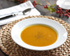 White Pillivuyt soup bowl filled with broth on round woven placemat