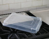 Quarter sheet pan cover sits diagonally on top of the quarter sheet pan and next to a half sheet pan on a stove.