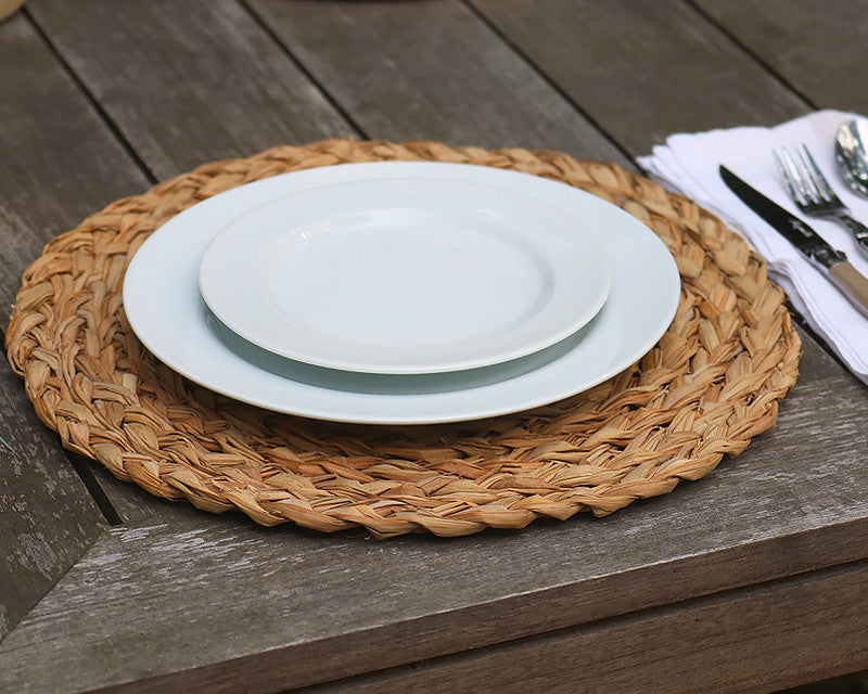 White dinner plate and salad plate stacked on round woven placemat
