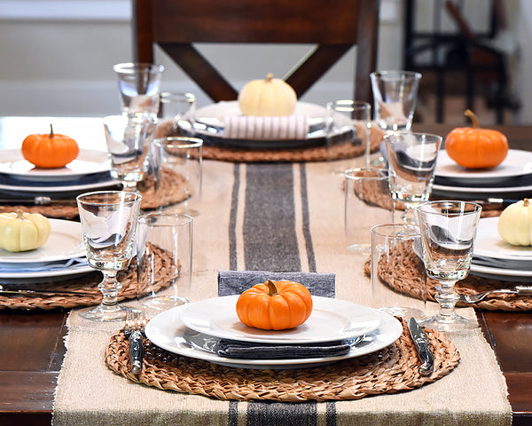 A beautiful fall table set with white plates, a small pumpkin on each plate and a navy stripe table runner.
