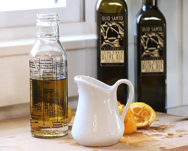 Salad Dressing bottle sits next to 2 bottles of Olio Santo Olive oil and a 9 Oz milk jug filled with lemon juice