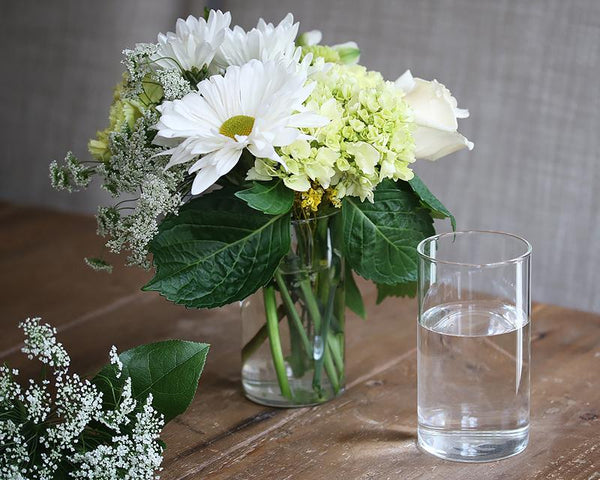 Simple water glass filled with fresh-cut flowers