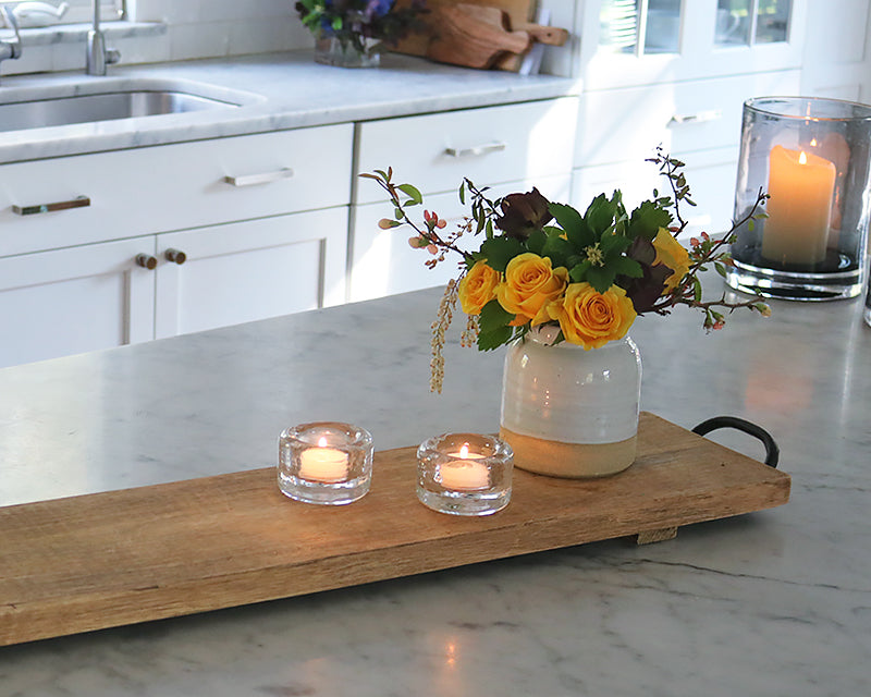 Clear glass tealight on a wood board next to a small vase of flowers.