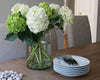 A stack of white Dessert Plates sit on a farm table with our everyday flatware in black. A vase of hydrangeas brightens up this simple table.