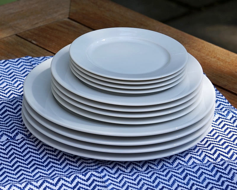 Pillivuyt white dinner plates, salad plates, and dessert plates stacked on striped placemat