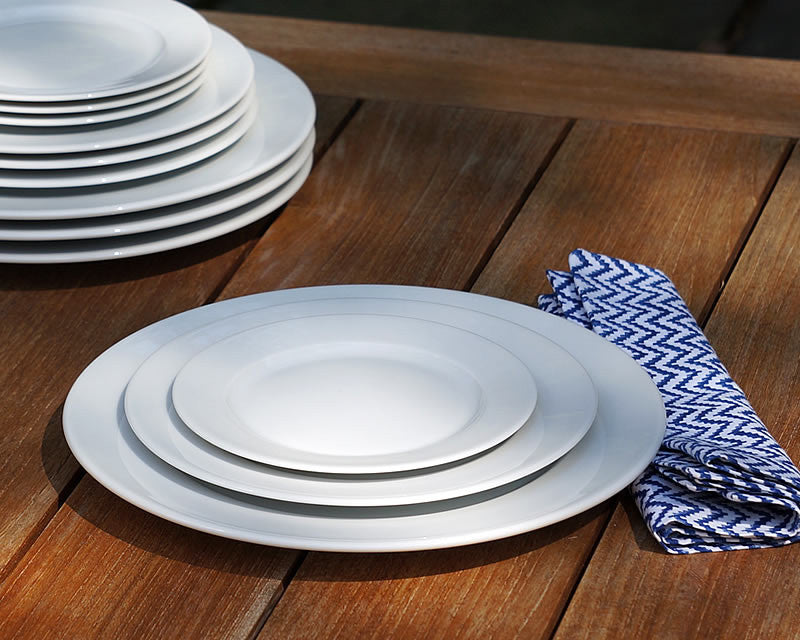 White dinner plates stacked on a wooden table
