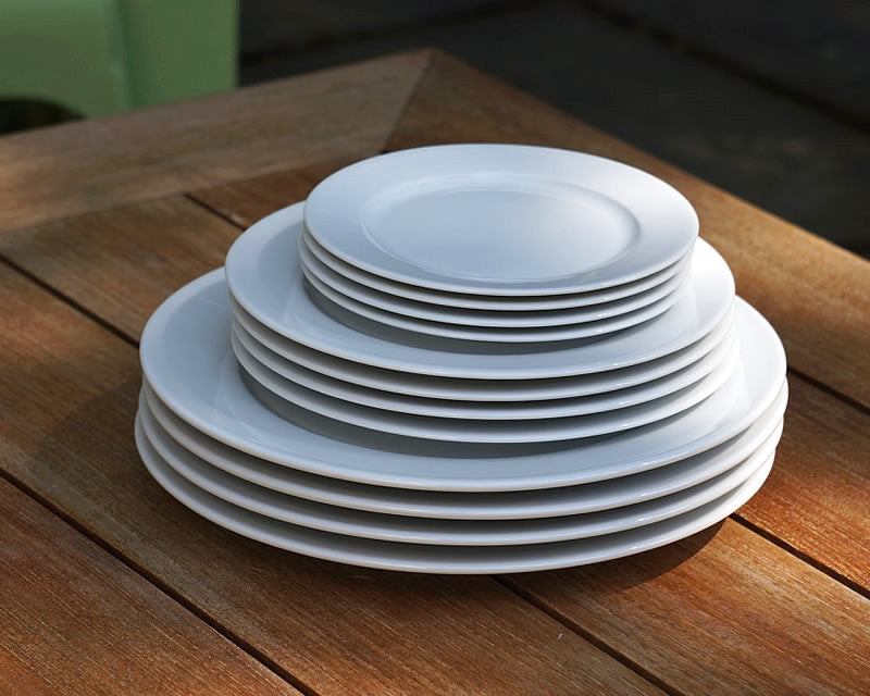 4 stacked sets of white Pillivuyt dinner plates, salads plates, and dessert plates on wooden table