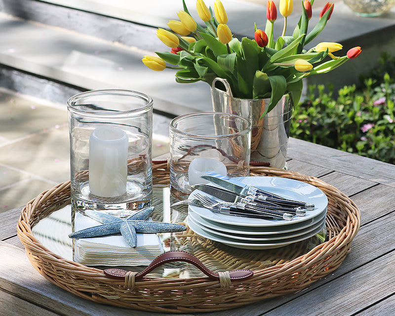 Beautiful outdoor setting ready for a party that includes our Woven Serving Tray, white dinnerware dishes, Everyday flatware, Clear Glass Hurricane Lamps and our Hotel Silver Wine Chiller filled with fresh cut flowers