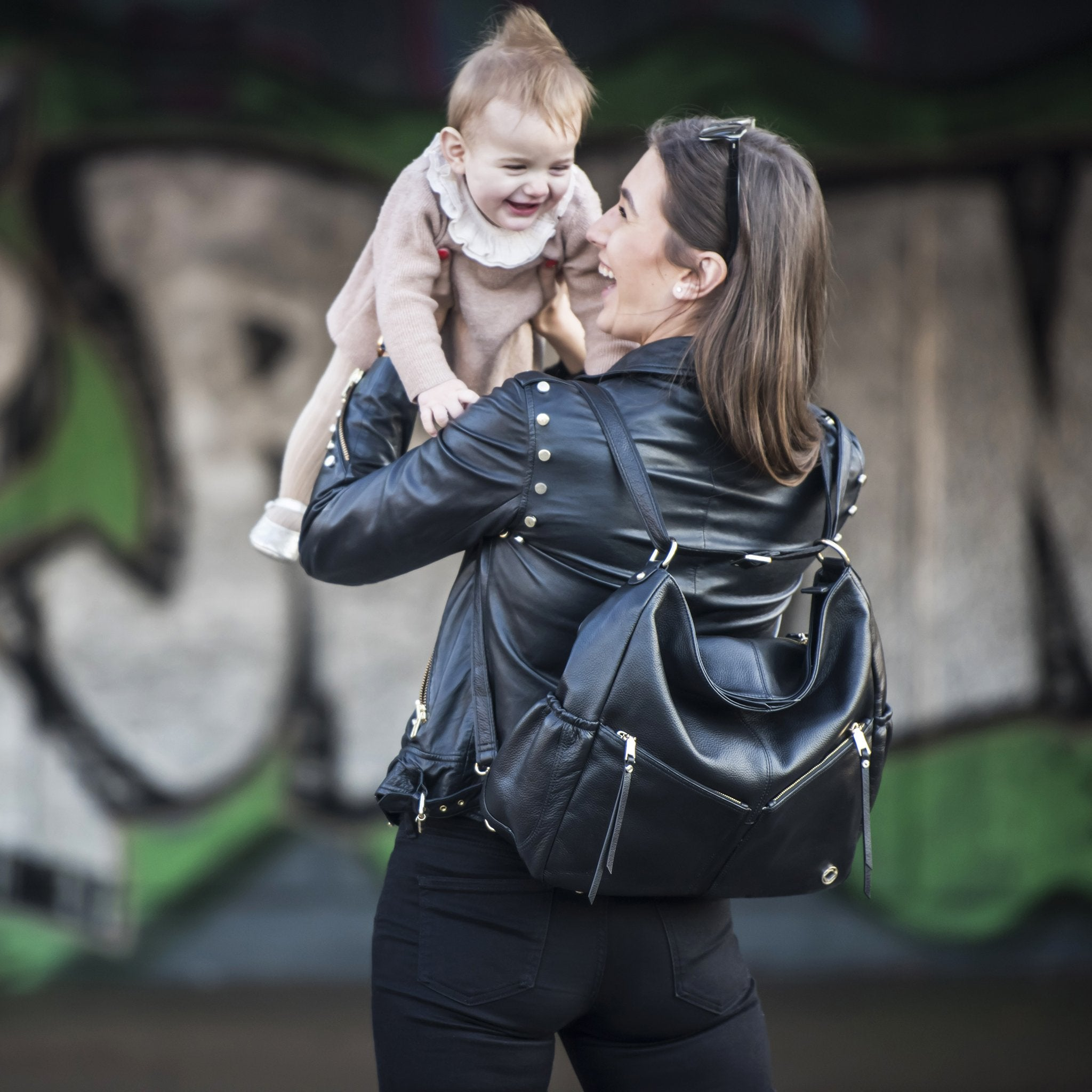 Lennox black leather changing bag. Image shows mother wearing black leather backpack with baby in arms.