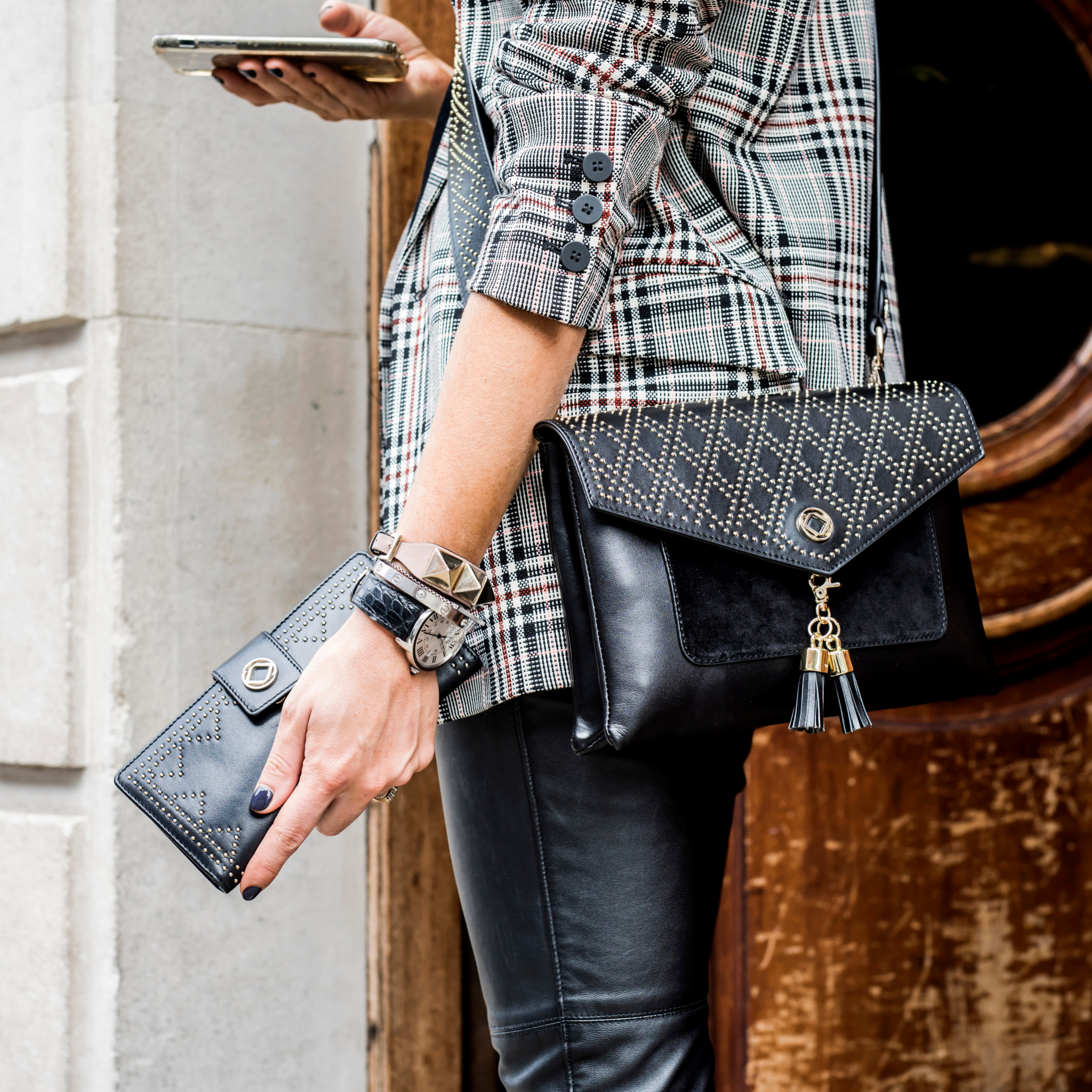Harry studded leather purse with a cross body strap. Image shows a lady wearing the Harry studded bag with a cross body strap while holding a studded Tilly purse that fits perfectly in your Harry handbag.