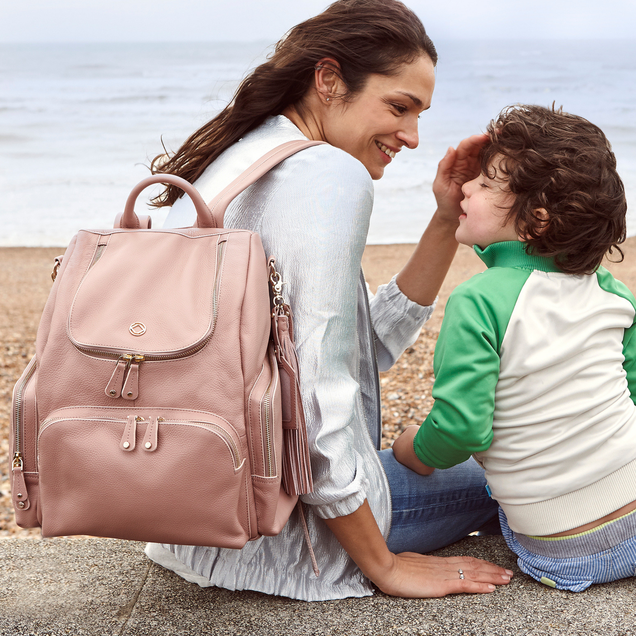 Amber Antique Rose Leather Backpack worn on back while sitting with child on beach