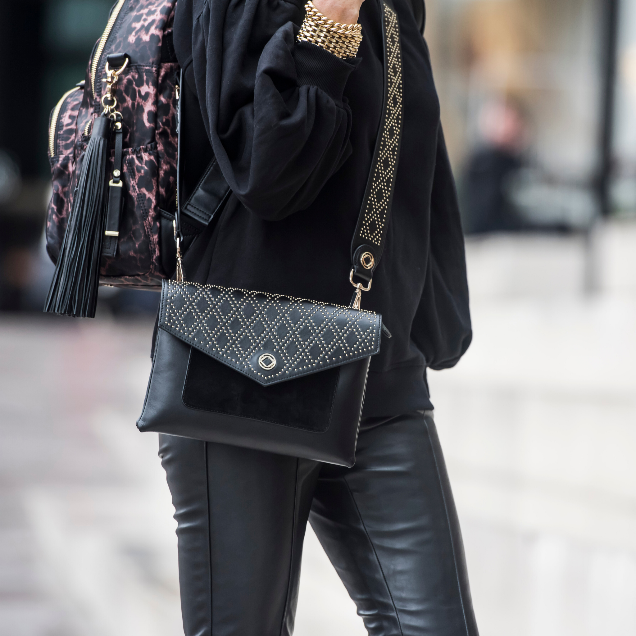 Black studded leather clutch easily carried underarm or across your body with a cross body strap attach to it. Image shows woman carrying purse as a handbag.