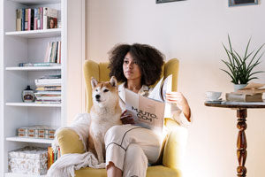 Woman in loungewear with dog and magazine