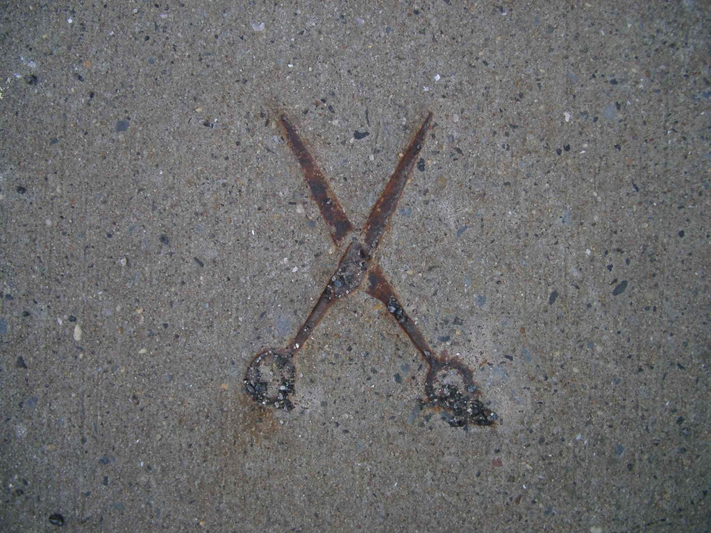 Old rusty scissors in the sidewalk