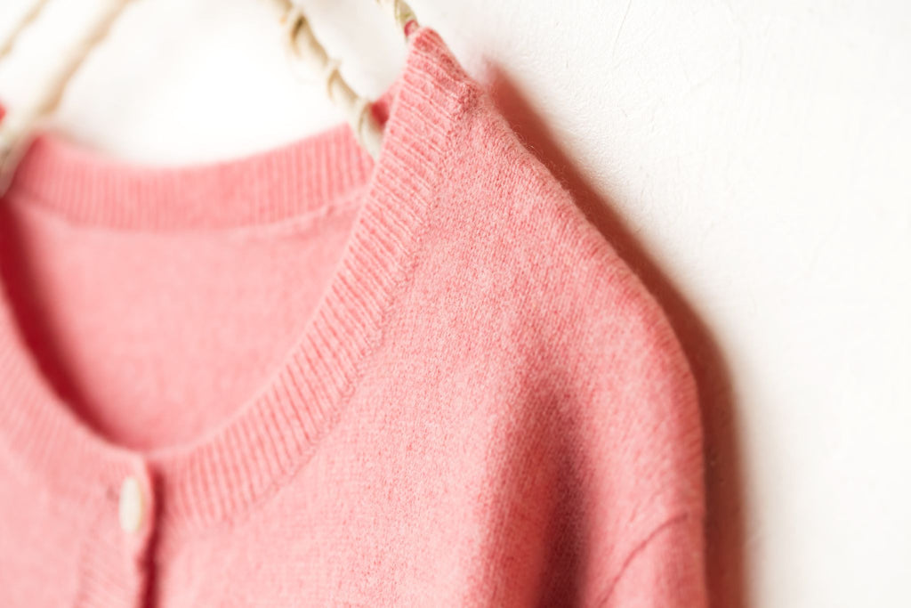 a blended wool pink cardigan on a hanger