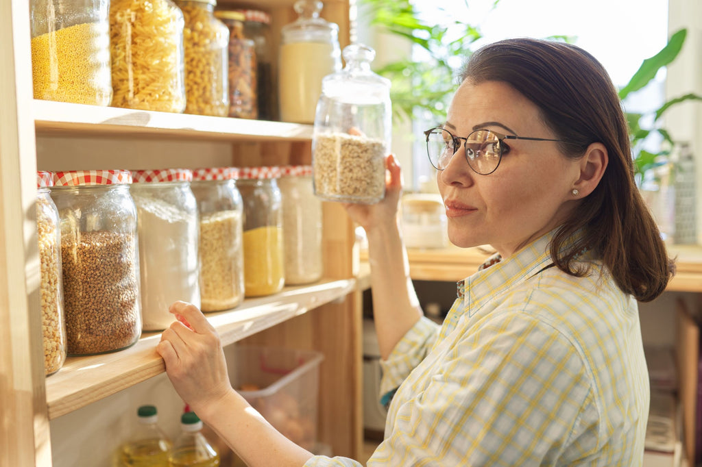 woman with shelves full of dried foodstuffs in sealed containers