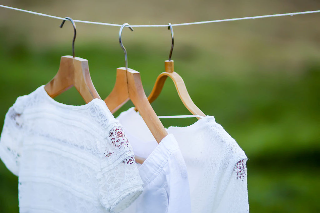 white linen garments on hangers airing outdoors