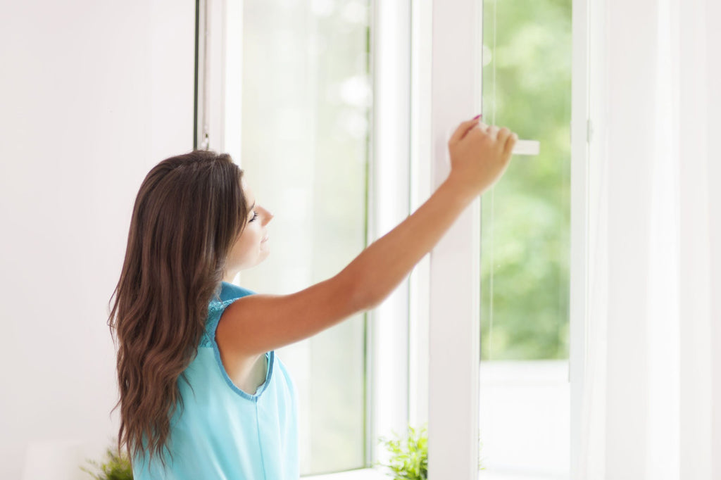 a woman opening the windows to air the room