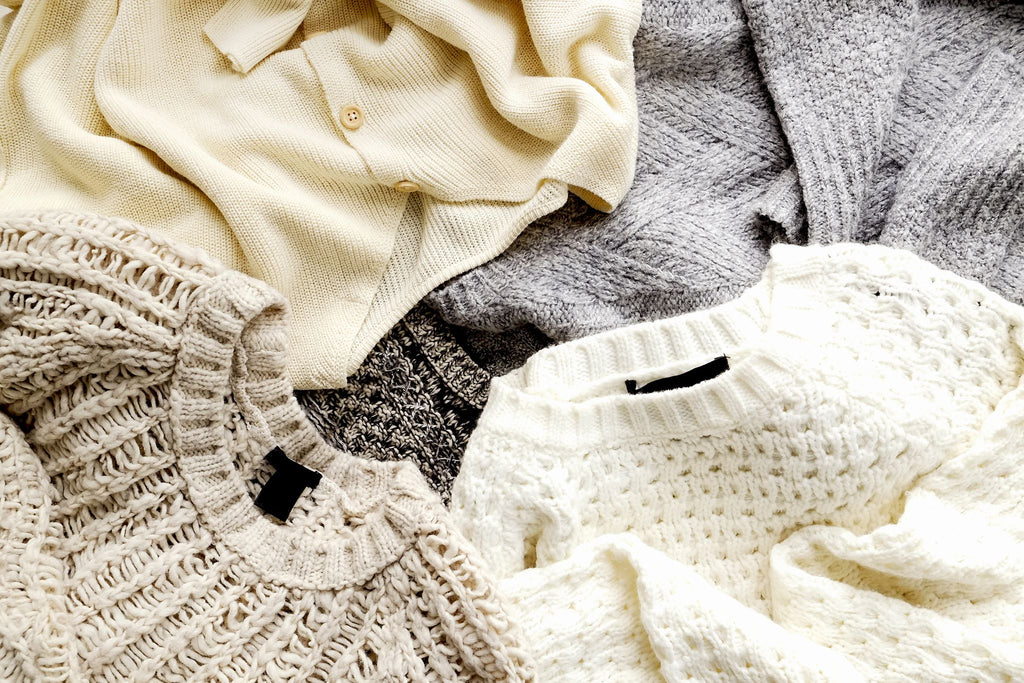 a selection of sweaters  loosely layered on top of each other