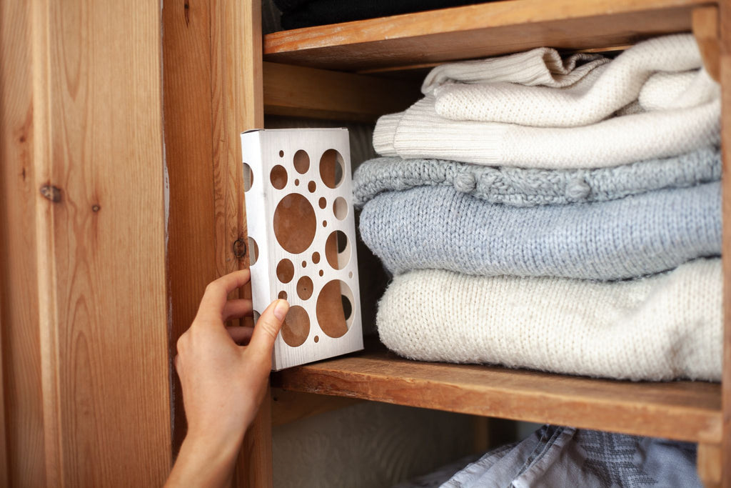 a sticky pheromone trap being placed on a closet shelf next to woolens