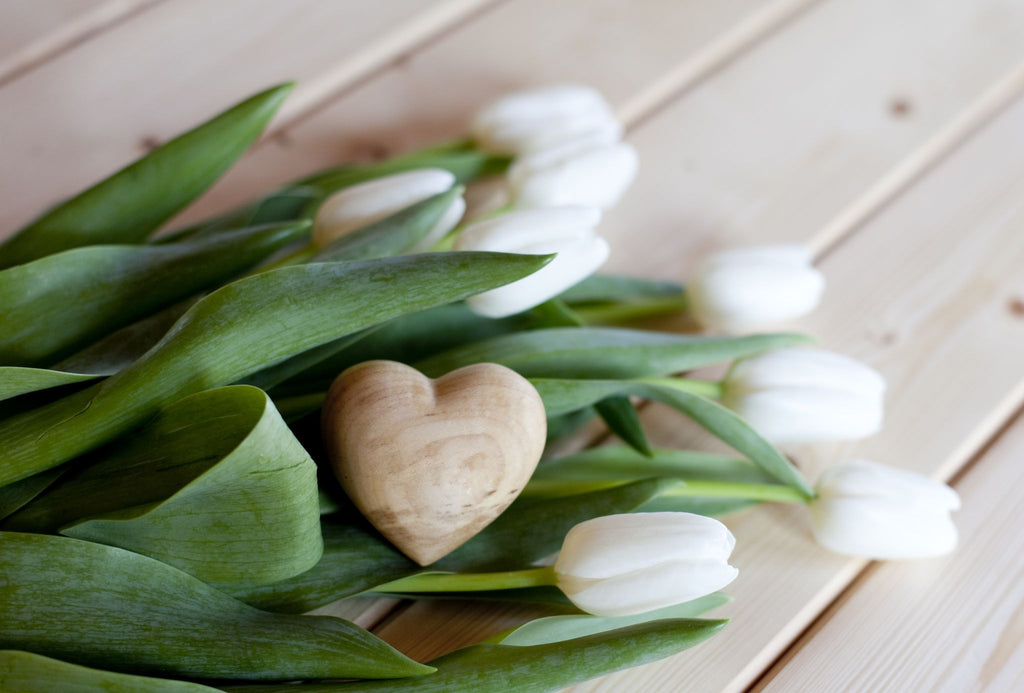 a heart shaped cedar block with white tulips