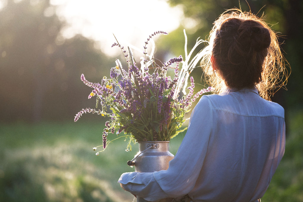 a woman carrying a churn of wild flowers and lavender