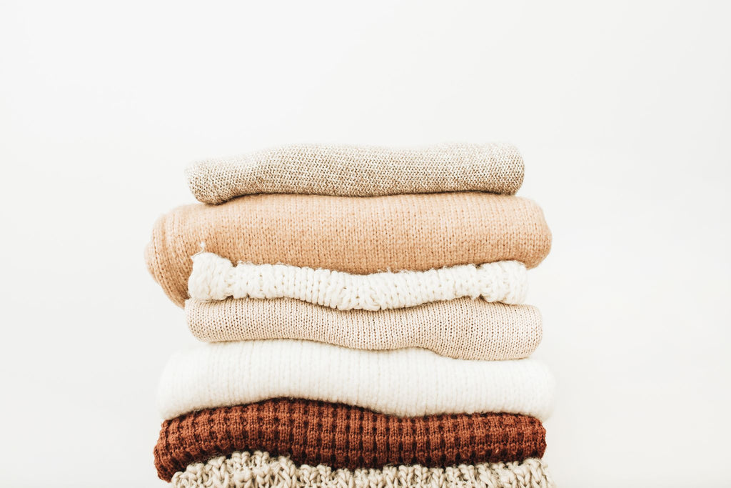 a pile of sweaters in brown and cream colors.