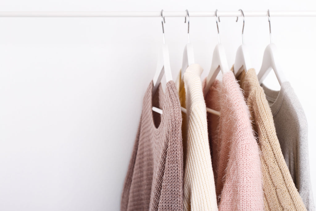 a selection of knitwear hung on white hangers on a rail