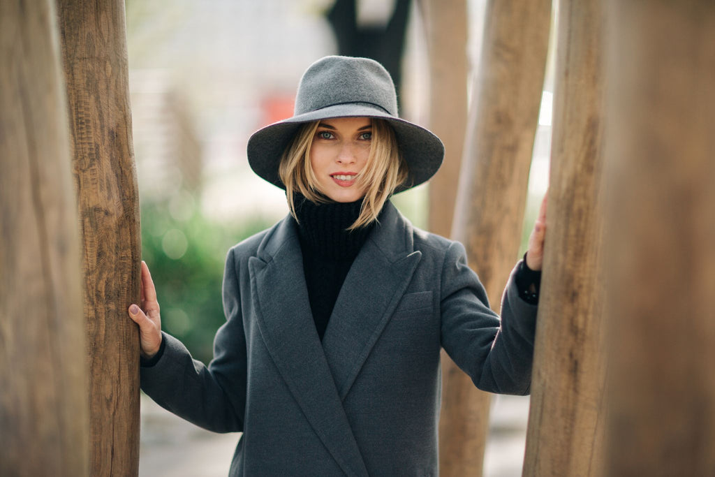 a woman standing between trees in a grey wool coat and hat