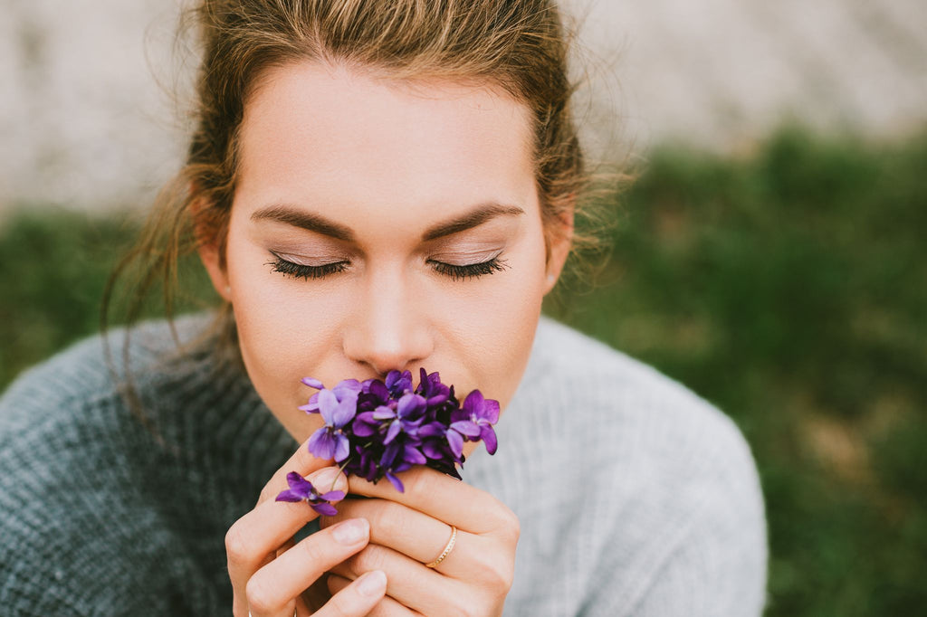 woman in a cashmere sweater smelling flowers