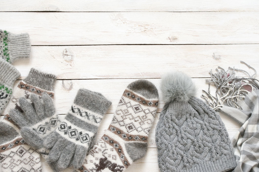 a selection of woolen gloves, socks and a bobble hat