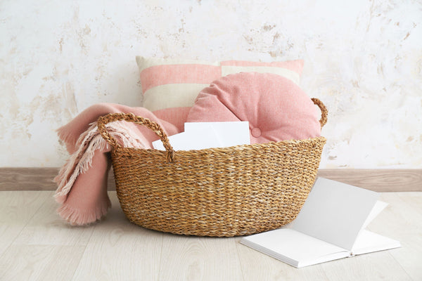 a wicker basket filled with cushions and a blanket