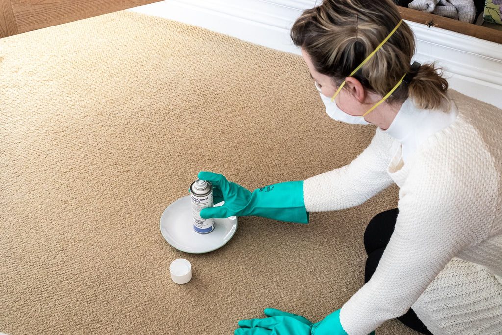 Moth Fogger being placed on the carpet by a woman wearing a mask and gloves