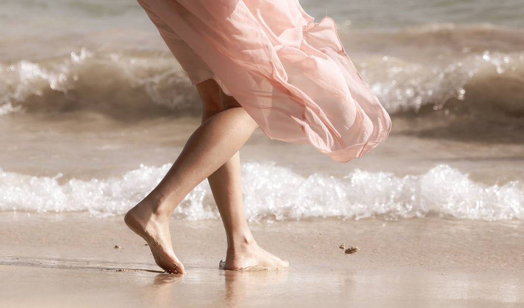 walking on the beach in a silk skirt billowed by the wind