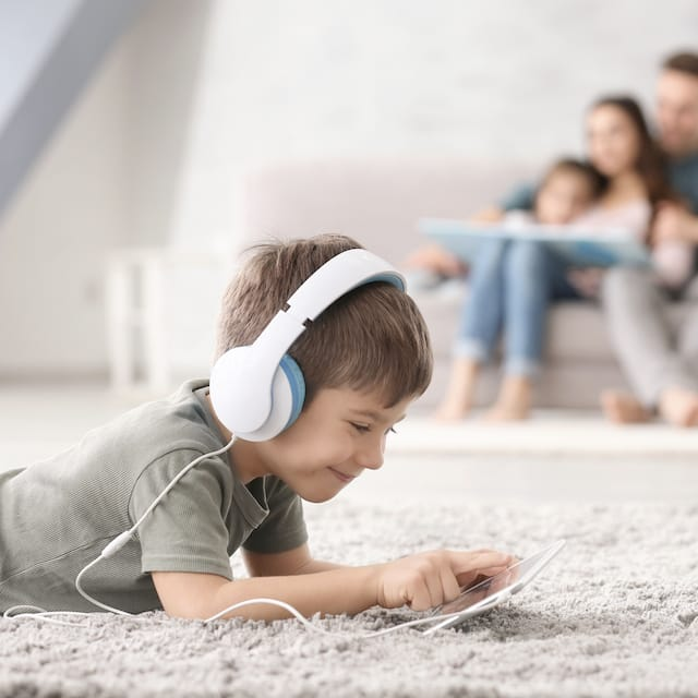 Child on carpet with family in background