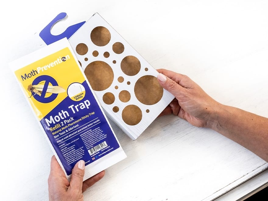 hands holding Moth Prevention trap and refill pack