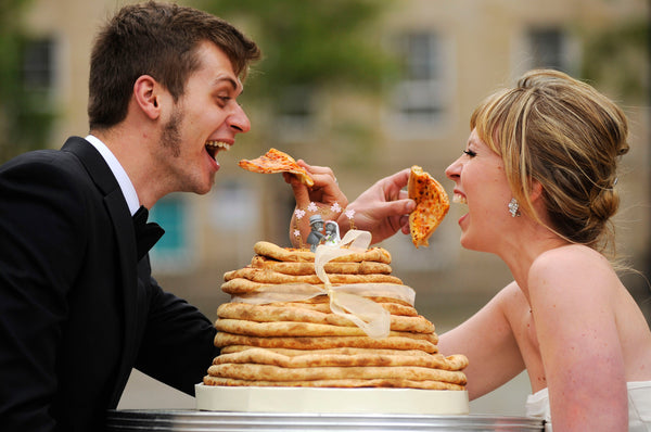 Bride and Groom Sharing a Pizza Wedding Cake