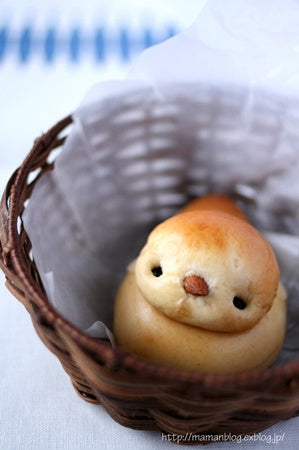 Adorable Chick Shaped Bread Roll peaking out of a wicker basket.