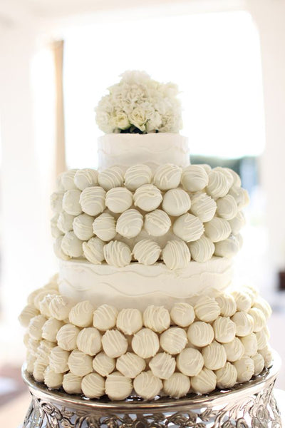 White Cake Pop Wedding Cake with Flower Arrangement on Top