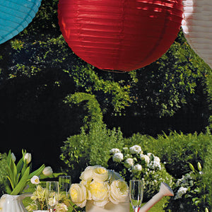 Round Paper Lanterns hanging outdoors above a table.