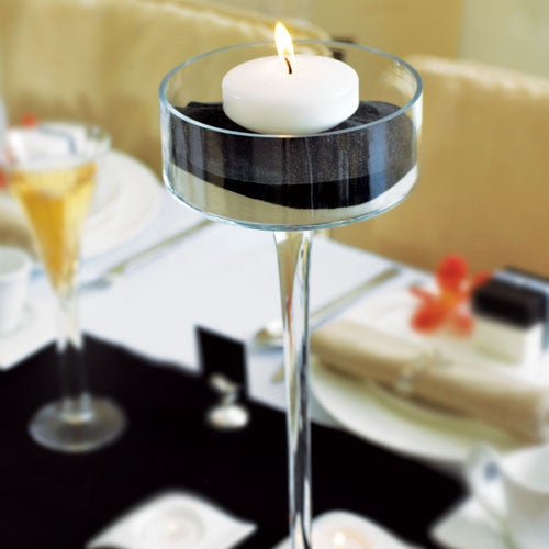 a small floating candles sitting in a glass centerpiece not included
